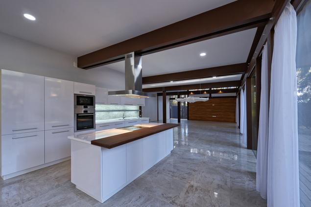 Biała, otwarta kuchnia z wyspą w stylu loftowym – nowoczesne wnętrze